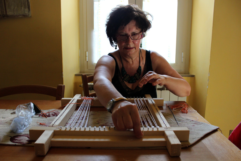 Patrizia Palazzetti, a weaver, demonstrates how to string a simple loom to create one of her colorful works of art. Photo taken in Cagli, Italy, on 18 June 2013. Photo by Deanna Titzler/Gonzaga in Cagli.